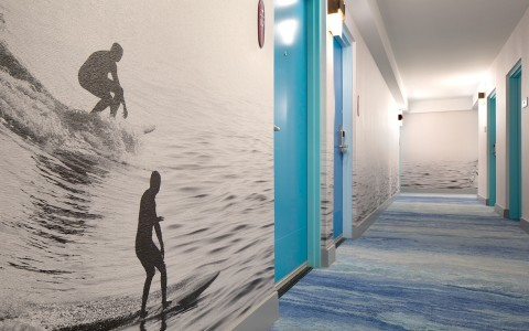 hallway with blue doors and surfer wallpaper