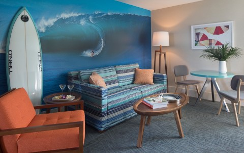 seating area with surfer mural and surfboard against the wall