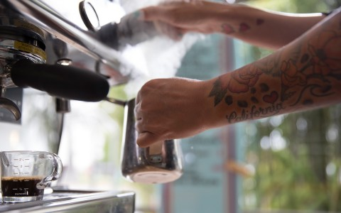 person with tattooed arms making an espresso at the coffee shop