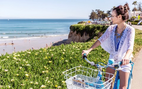 girl with flowy white top on rental bike on path looking at ocean