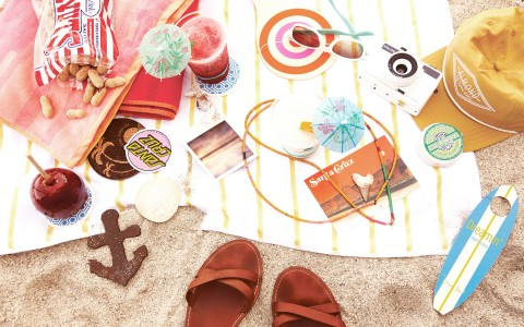 beach towel with sandals, mini surfboards, peanuts, sunglasses and a hat