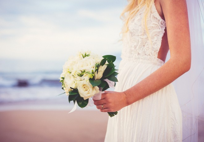 blonde bride on beach with white rose bouquet