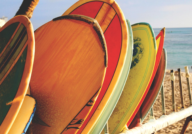 colorful surfboards stacked on surf rack