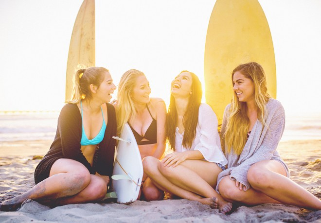 4 girls in their twenties sitting on beach laughing with surfboards behind them