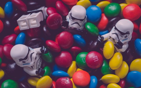 storm trooper toys thrown in a pile of colorful m and m candy
