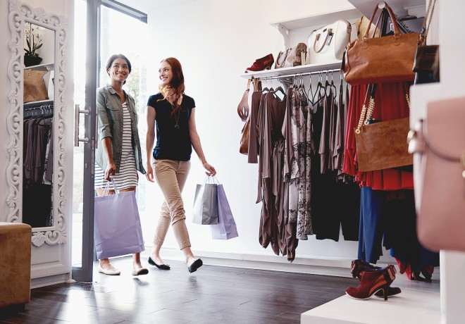 Two ladies walking into a clothing store with shopping bags