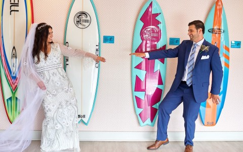 bride and groom in front of surfboards
