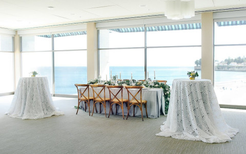 head table set up flanked by two round cocktail tables in a ballroom with floor to ceiling windows