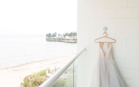 wedding dress hanging on the balcony overlooking the beach