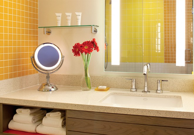 bathroom in guest room with yellow tiles and fresh red flowers