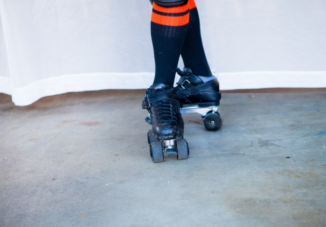 Close up of person wearing roller skates and tall black and orange socks
