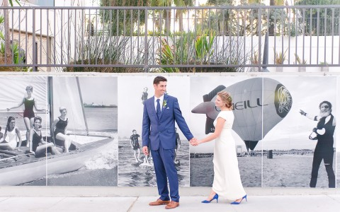 bride and groom in front of a black and white mural