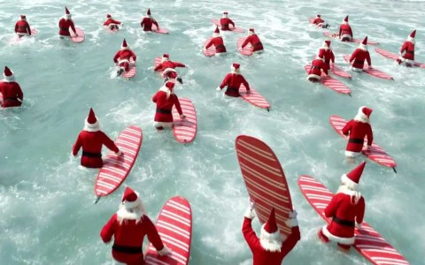 a large group of santas on candycane surfboards in the ocean