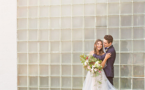 bride and groom posing on the beach in front of vintage glass wall