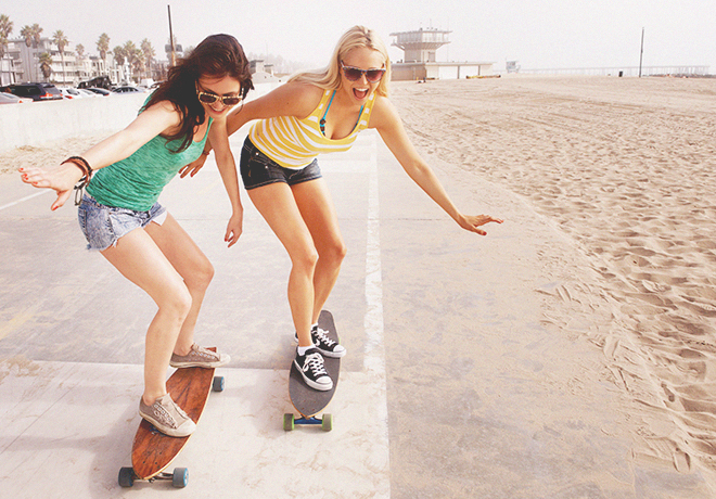 Two girls riding longboards on the beach boardwalk