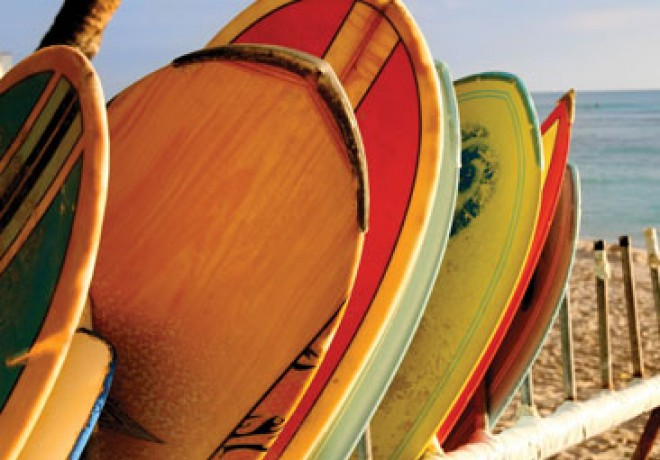 colorful surfboards stacked up in a surf rack