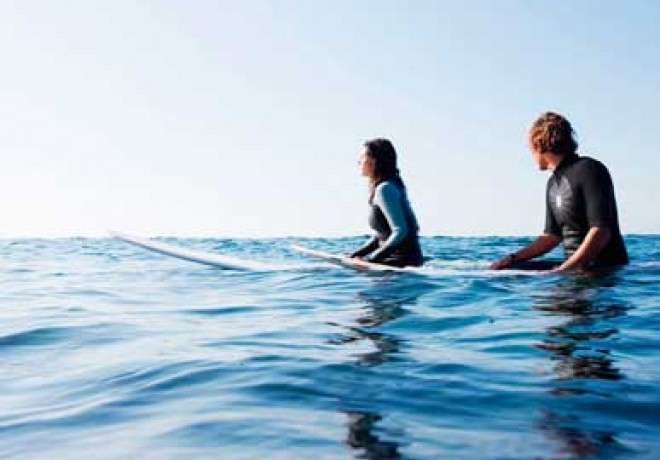 two surfers sitting on surfboards in the blue water