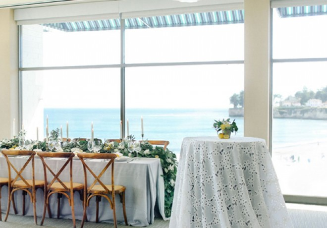 ballroom set for a wedding with a small cocktail table and a longer dining table with garland overlooking the beach