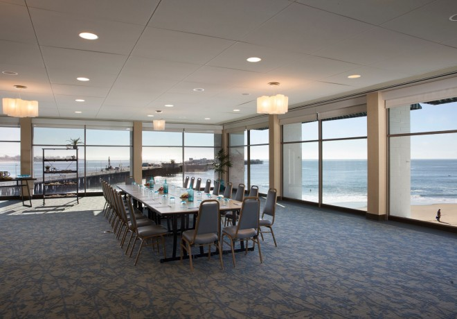 large room with floor to ceiling windows and a long table set for a board meeting