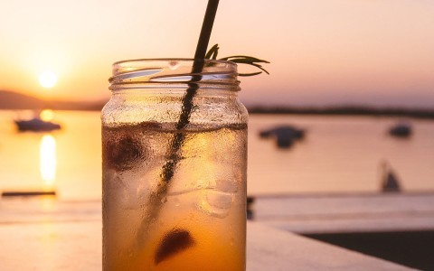 Mason jar with iced tea and ice with boats on the water in the background blurred out