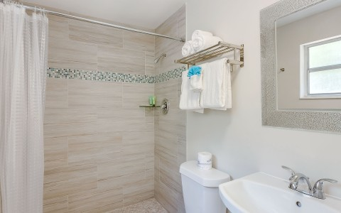 Bathroom with light brown tiled shower, white toilet and sink