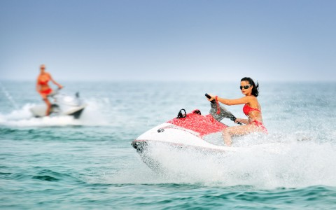2 women on jet skis, one in front looking towards camera wearing sunglasses