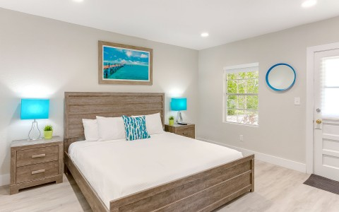One bed with white bedding, one blue accent pillow and two matching blue lamps
