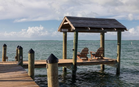 two chairs under roof on dock over ocean