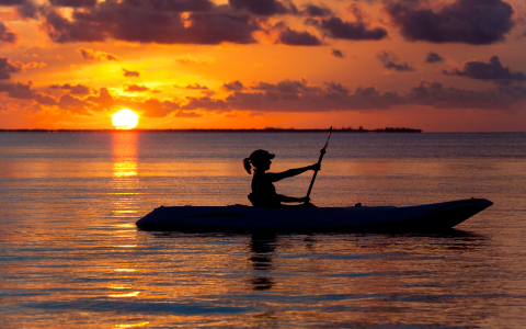 woman kayaking with sunset behind her