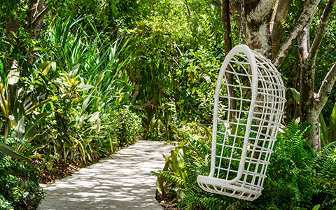 garden pathway with swinging white chair