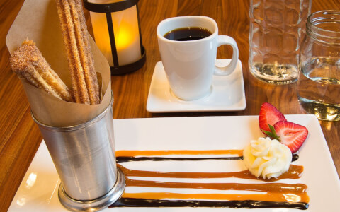 Churros in metallic container on plate with drizzled sauces next to a coffee cup