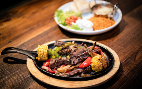 Close up of fajitas dish on wooden table