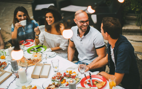 Group of friends gathered at tables with plates of shareable appetizers