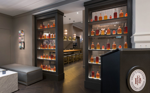 Entrance to restaurant with hostess podium next to shelves of display bourbon bottles