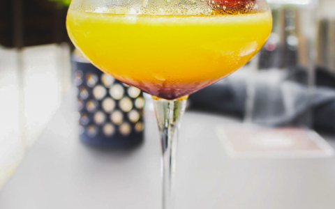 Yellow cocktail with strawberry placed on the edge of glass