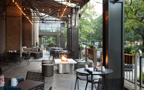 Outdoor seating with black metallic tables & chairs with stringed lightbulbs and a fire pit in the center