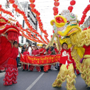 Two boys carrying lion and dragon displays during Chinese New Year Parade