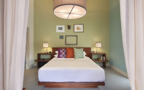 Room with double bed, colorful pillows, wooden bed frame, nightstands, frames on wall & canvas ceiling lamp