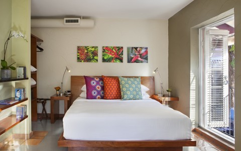 Room with queen bed, colorful pillows, tropical flower wall art, wooden nightstands & opened balcony door