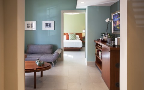 Room living space with couch, wooden furniture, teal wall & bedroom doorway