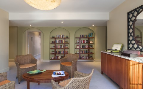Lobby seating area with wicker chairs, wooden furniture & built in book shelves in the back
