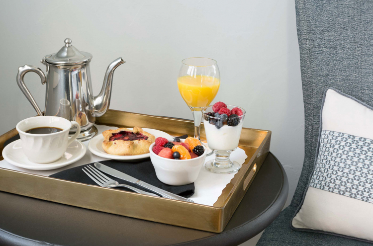 small breakfast tray sitting next to side of couch