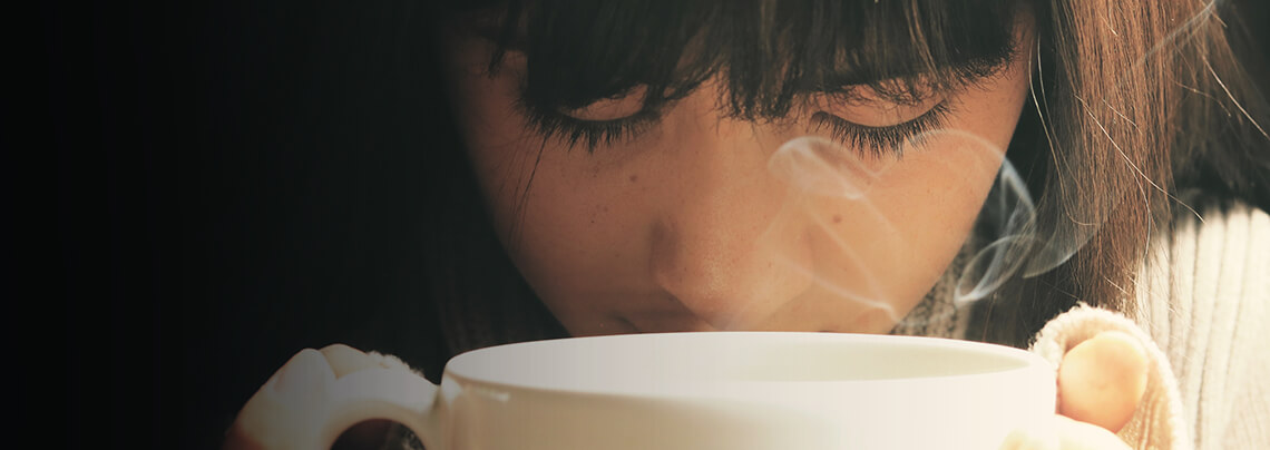 woman smelling her hot coffee