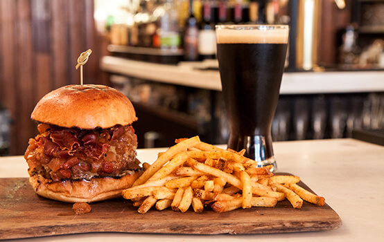 Burger with fries and a pint of dark beer