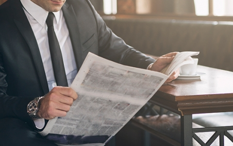 business man reading a newspaper while drinking a cup of coffee