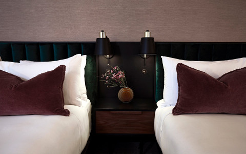 hotel bedroom with black headboard and lamp, white sheets, and purple pillows