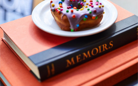 sprinkled donut on plate on top of two stacked red books