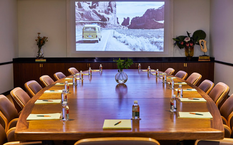 conference room with wooden desk, water bottles, and projector screen