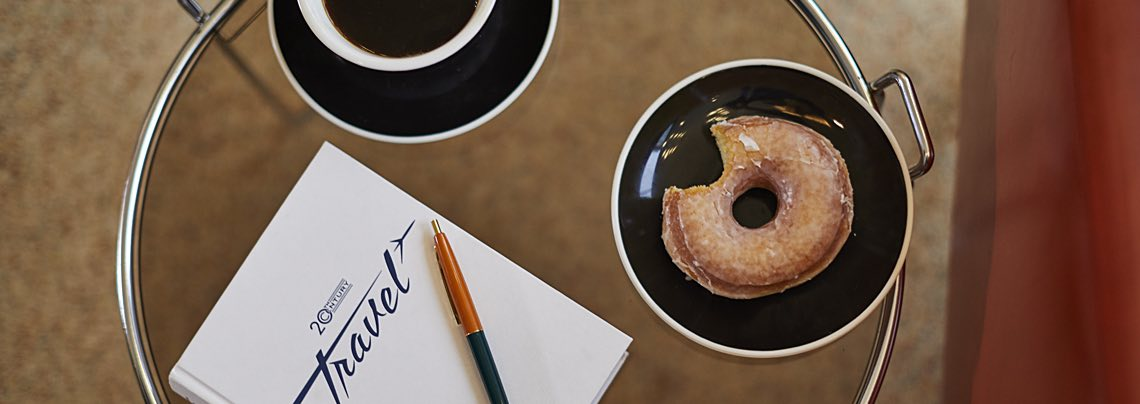 Glass table with donut, coffee and notebook