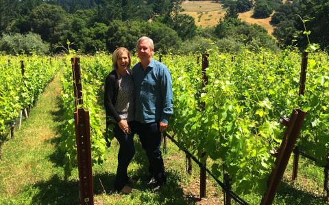 Couple standing in front of grape vines